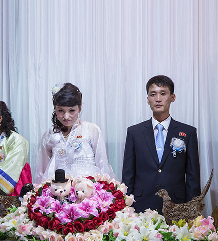 North Korean groom and bride in front of the wedding cake