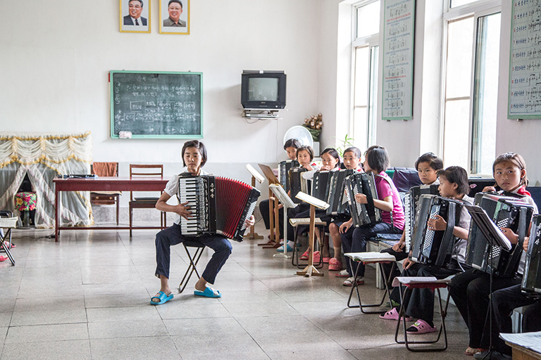 An accordion class at the Kaesong Childrens' Palace, aka, extracurricular activity jail, where children are assigned activity or skill in the same way they will be assigned a job later in life. He'll be a singer, she'll play the accordion, and they will practice every single day of their lives.